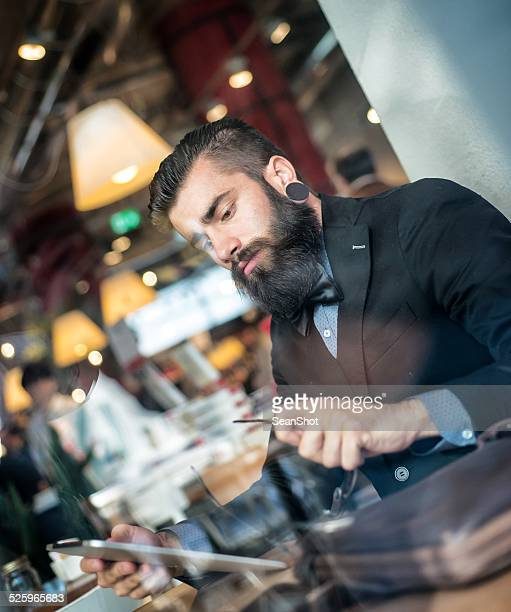 Hipster Uomo d'affari utilizzando un Tablet in un caffè