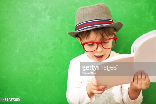Hipster Child Reading a Book on Green Background