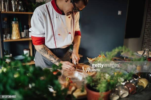 Hipster cook preparing Caesar's salad