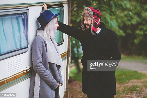 Hipster couple in front of wooden house