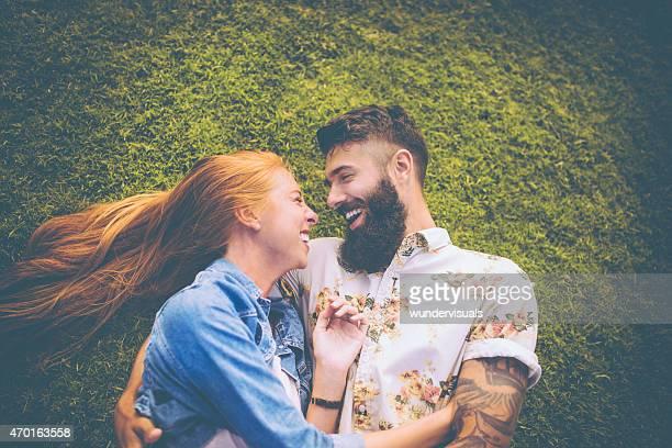 Hipster pareja acostado de hierba afectuosamente abrazándose