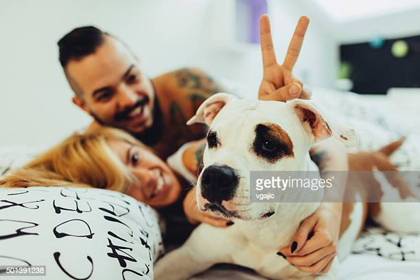 Hipster Couple Waking Up With Their Dog.
