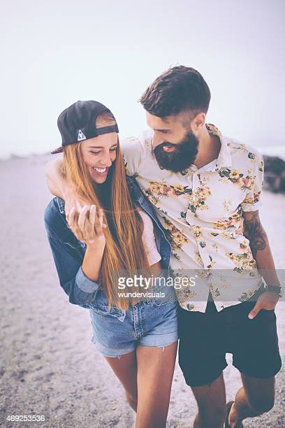 Hipster couple walking together and holding hands on a beach