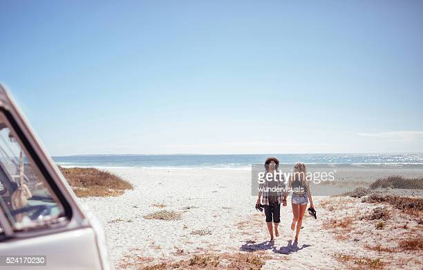 Hipster couple walking together barefoot towards van from beach