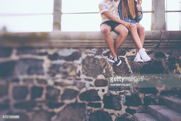 Hipster couple's legs sitting on a stone wall