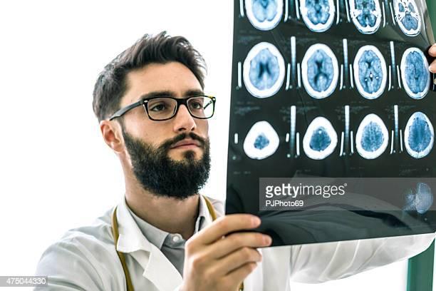 Hipster médico examinar las radiografías del cerebro