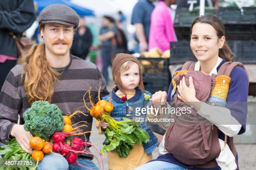 Hipster family buying produce from outdoor farmers market