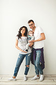 Young hipster father, mother holding cute baby boy on rustic wooden floor over white background