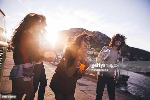 Hipster amis s'amuser avec des bulles dans le port au coucher du soleil