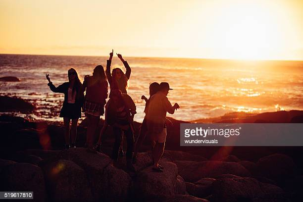 Hipster friends dancing and partying at sunset at beach