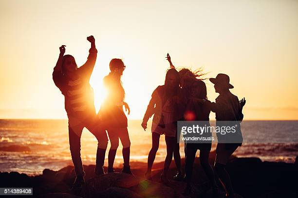 Hipster friends dancing in sunset light at a beach