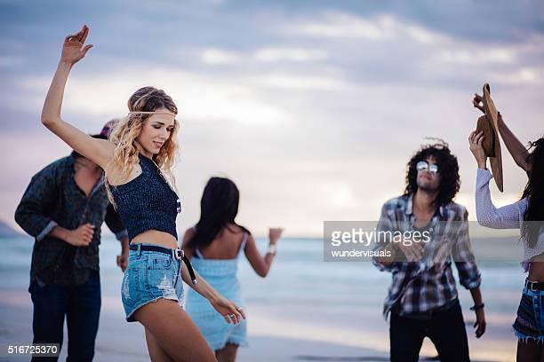Hipster amis danser sur la plage de sable fin en bord de mer