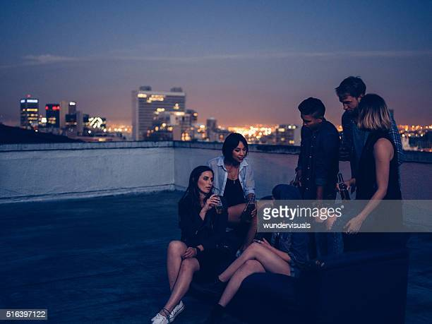 Hipster friends drinking and talking on a rooftop party