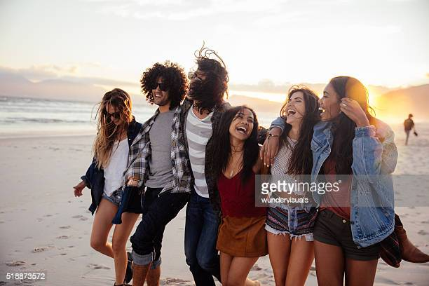 avec joie Hipster amis embrassant au coucher de soleil en bord de mer