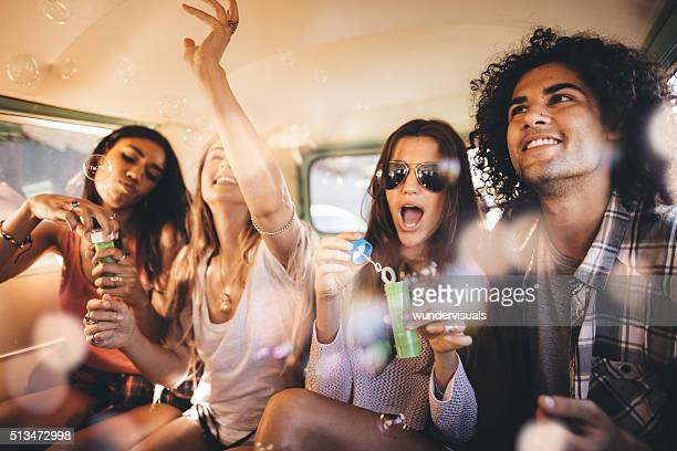 Hipster friends having bubbles party inside a vintage van