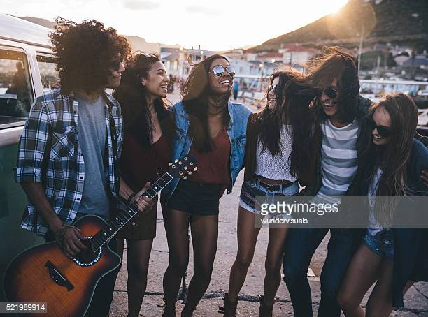 Hipster friends having fun with a guitar on road trip