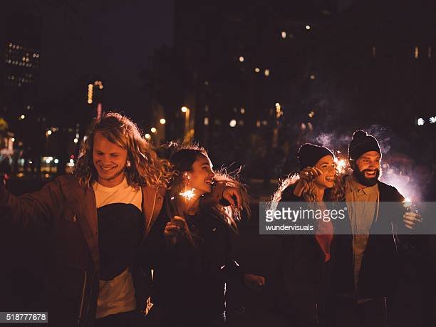 Hipster friends having night party with sparklers in the city