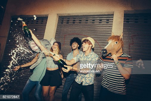 Hipster Friends Popping Champagne In Street