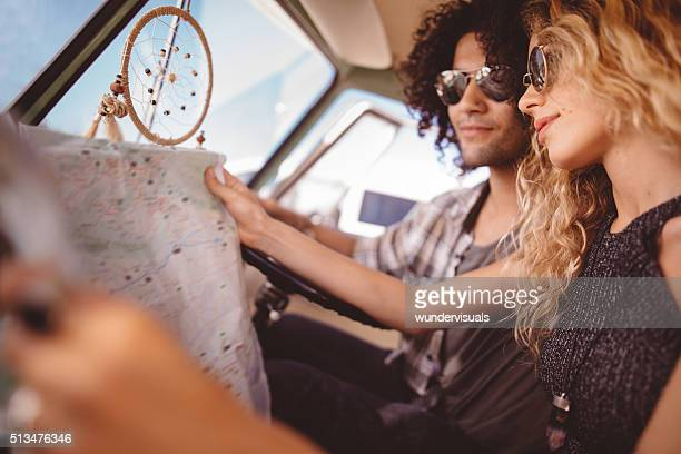 Hipster Friends Sitting in Retro Van Looking at Map