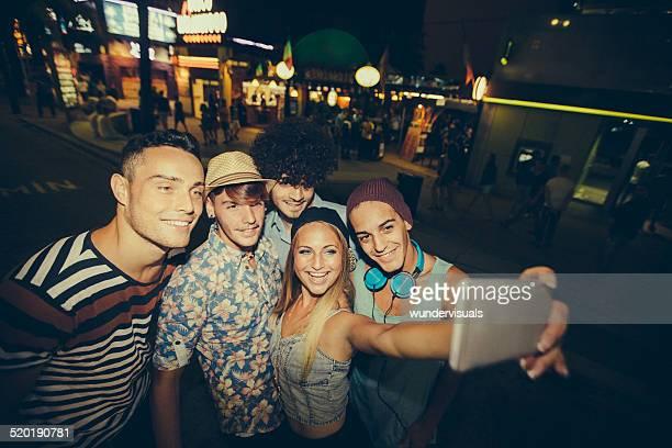 Hipster gli amici prendendo Selfie In strada di notte