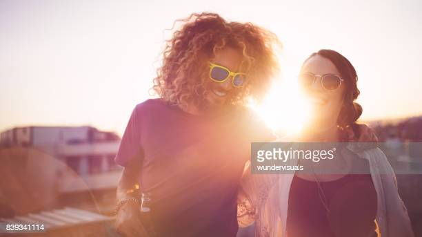 Hipster friends with drinks laughing at summer rooftop party