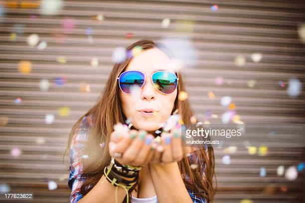 Hipster girl blowing confetti from hands