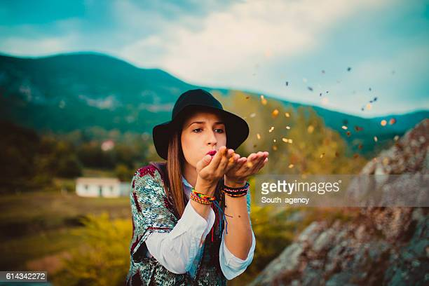 Hipster girl blowing confetti