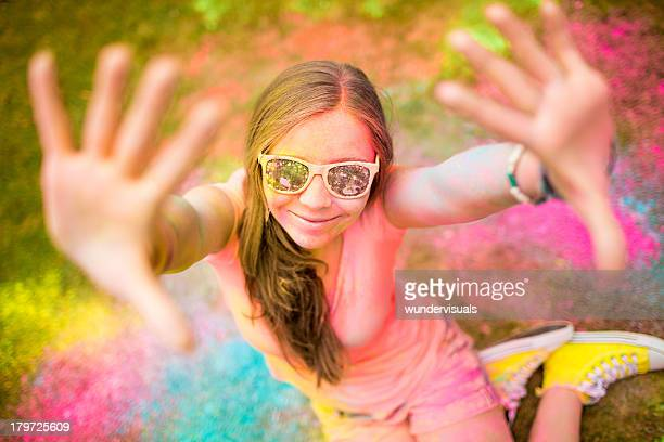 Hipster girl celebrating Holi Festival with colorful powder