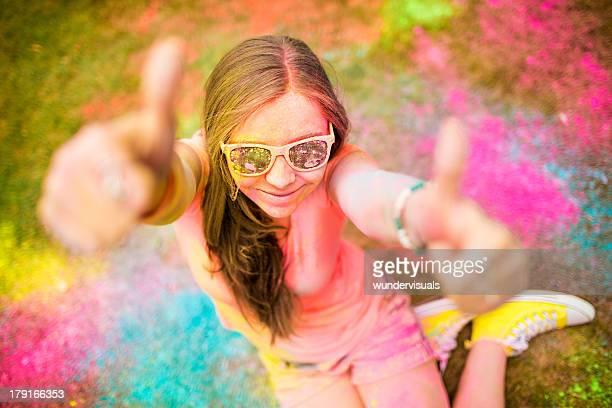 Hipster Mädchen geben Daumen hoch auf bunten Holi Festival