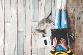 Hipster lifestyle and Creative workspace - Girl in jeans working on the laptop computer assisted by her cat on the wooden floor. vintage film color effect and retro color style