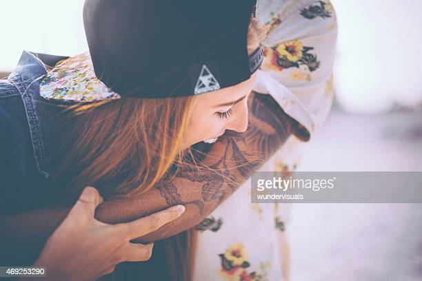 Hipster girl playfully pretending to bite her boyfriend's tattoo