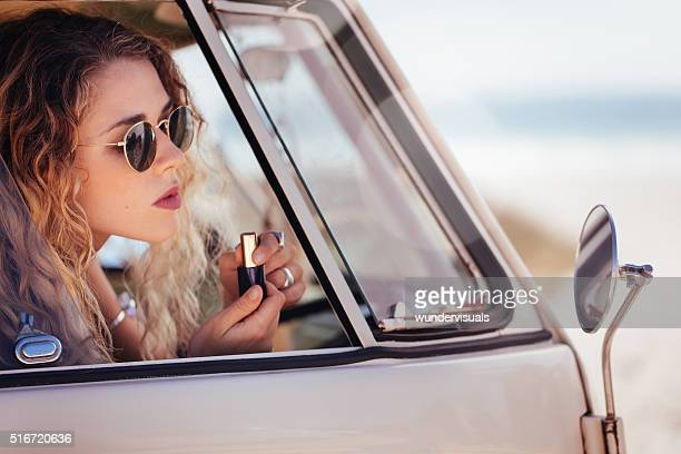Hipster Girl Putting on Lipstick in Sideview Mirror of van