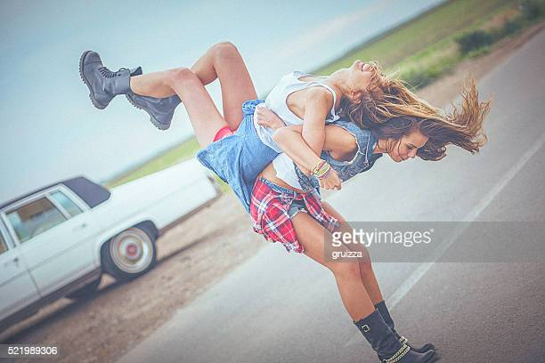 Hipster Mädchen Reiten auf Ihre weibliche Freund Huckepack nehmen.