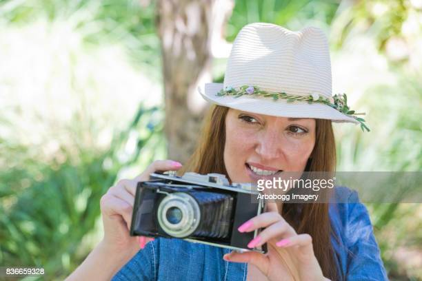 Hipster girl taking photos with her retro camera