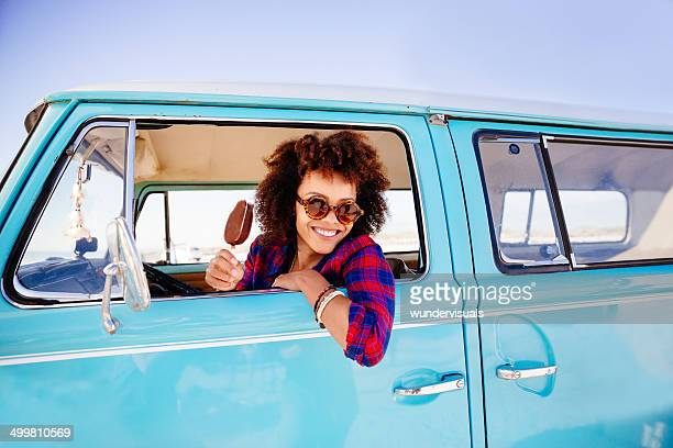 Hipster girl with icecream in camper van