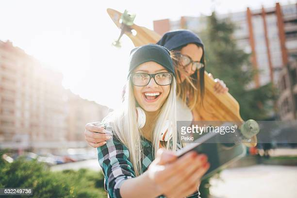 Hipster girlfriends taking a selfie in urban city