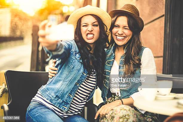 Hipster girls having fun and taking selfies in a cafe