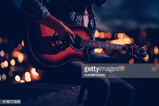 Hipster guitarist playing on a rooftop at night