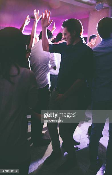 Hipster guy dancing with friends in a club