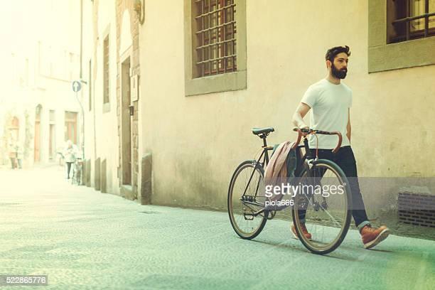 Hipster Kerl zu Fuß, mit dem Fahrrad