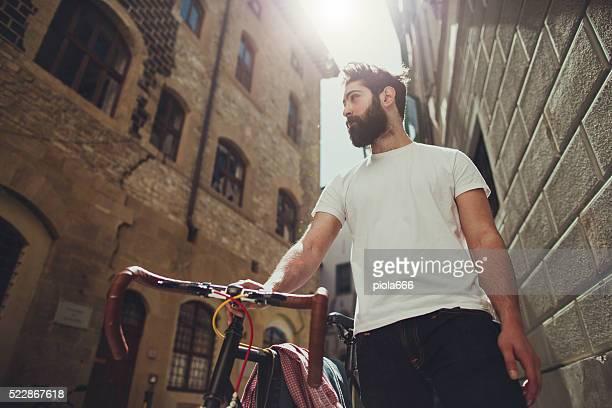 Hipster uomo a piedi con la bicicletta