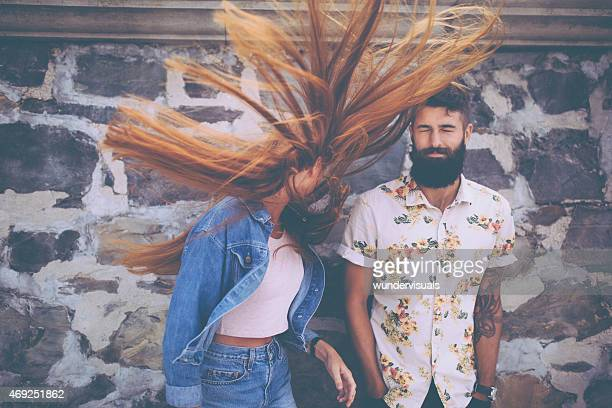 Hipster guy with hipster girl flinging her hair wildly