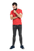 Young hipster in red t-shirt stroking beard while thinking and looking down. Full body length portrait isolated over white studio background.