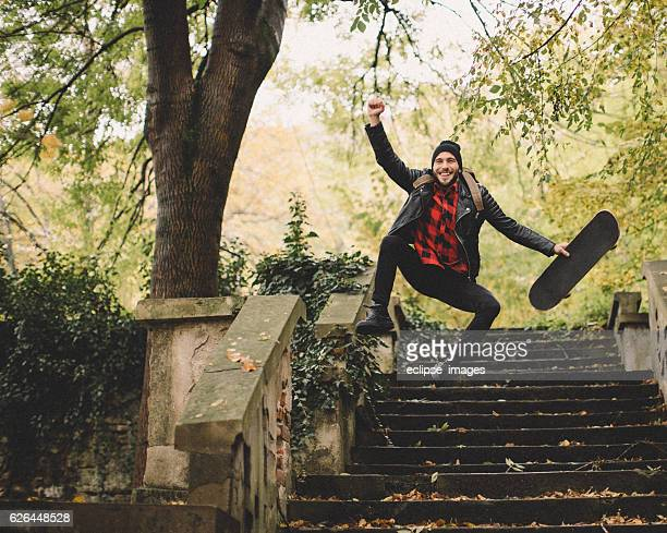 Hipster jumping with skateboard