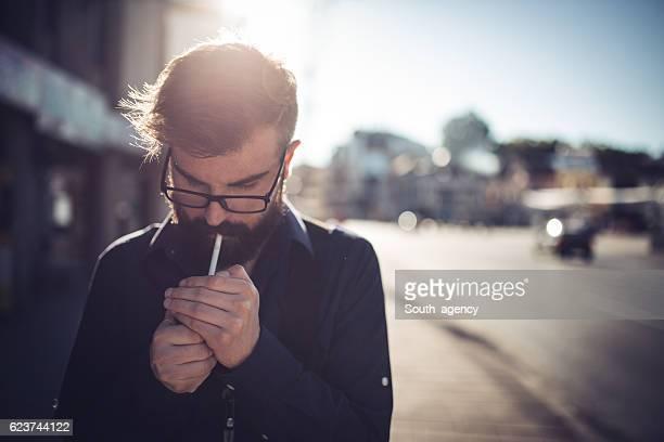 Hipster lighting a cigarette