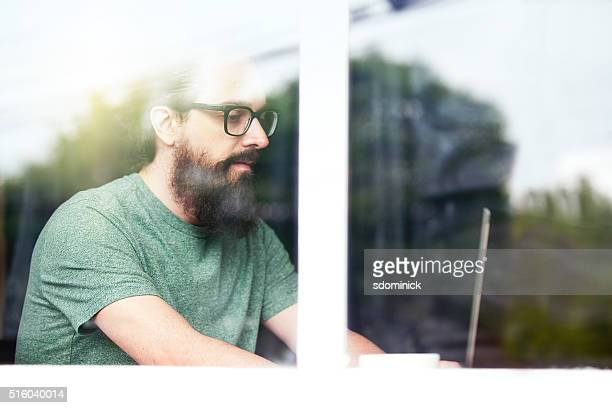 Hipster Man Behind Window Working On Laptop