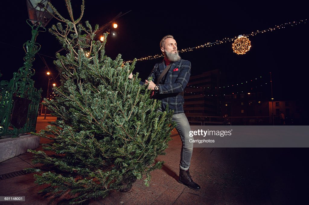 hipster man holding a christmas tree stock photo getty images
