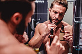 Hipster shirtless man holding bottle in the bathroom
