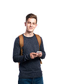 Hipster teenage boy in eyeglasses, jeans and striped sweater, holding smart phone, making phone call. Young man. Studio shot on white background, isolated.