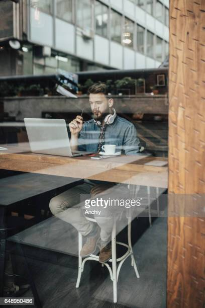 Hipster man in cafe working on laptop by window